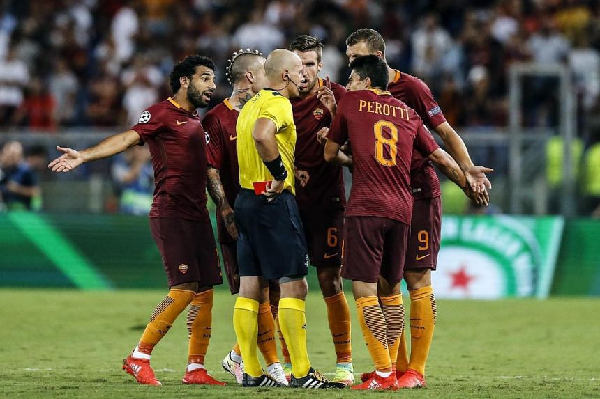Referee Szymon Marciniak (centre) talks with Roma's players after issuing a red card during the UEFA Champions League qualification playoff round second leg soccer match between AS Roma and FC Porto at Stadio Olimpico in Rome, Italy on Aug 23.