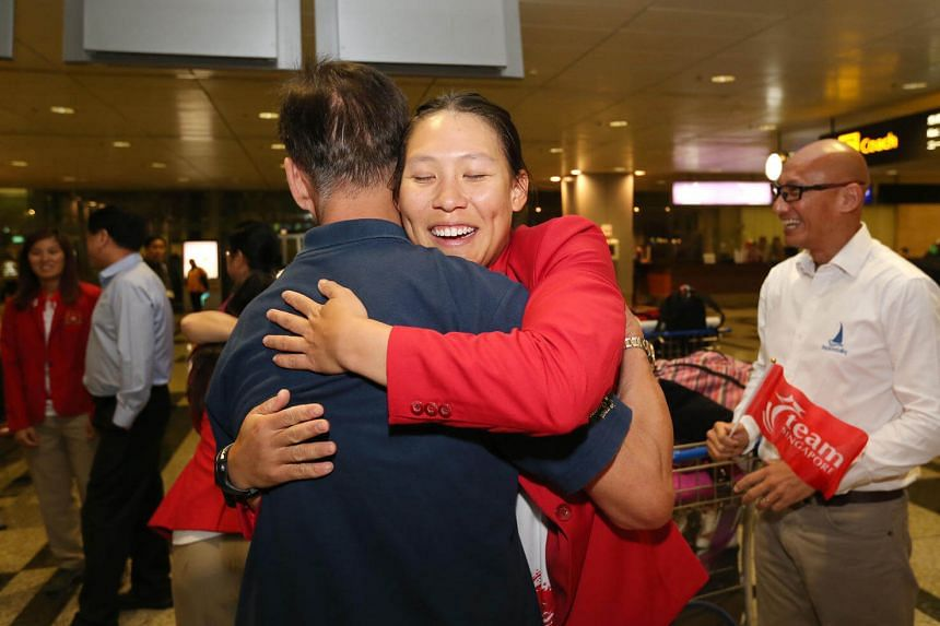 A family member welcomes sailor Sara Tan as Team Singapore's final batch of Olympic athletes, the sailing team returns from Rio at Changi Airport Terminal 3 on August 24.