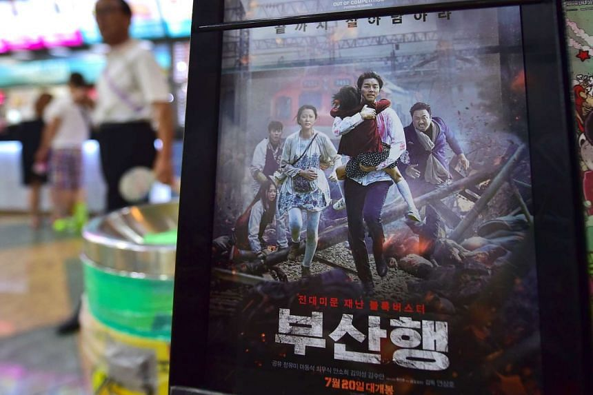 A man walks past a poster of Train To Busan at a movie theatre in Seoul on Aug 4, 2016.