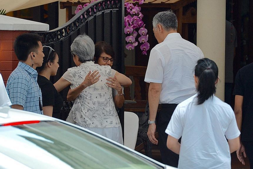 Above: Mrs Lee Hsien Loong exchanging a hug with Mr Nathan's daughter Juthika as she and PM Lee arrived at the former president's home in Ceylon Road yesterday. Below: PM Lee leaving after paying his respects. Mrs Nathan did not step out into the gla