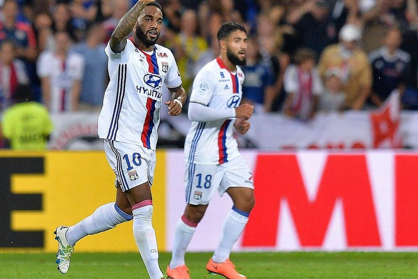 """Alexandre Lacazette (left) celebrates after scoring for Lyon on Friday. The striker has reaffirmed his commitment to the French club, saying: """"There will be no departure. Everything is going well here."""""""