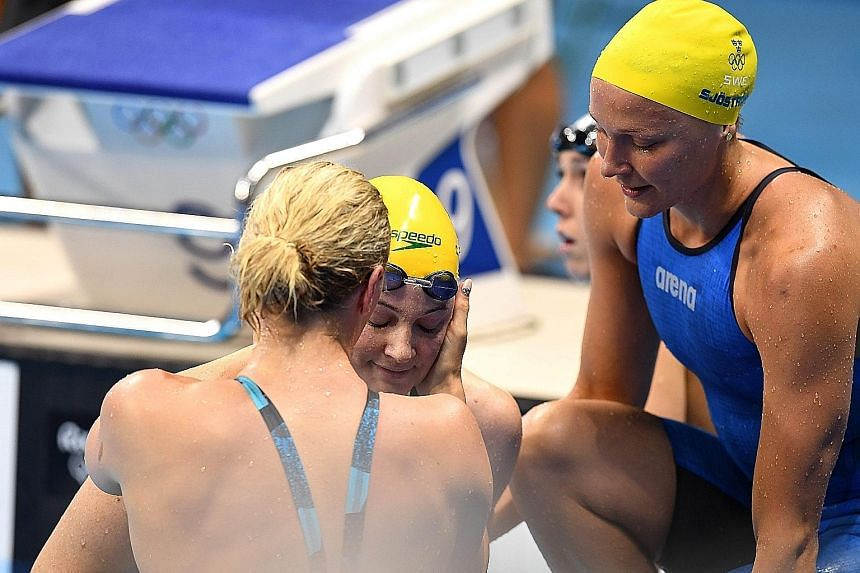 Cate Campbell of Australia (centre) is consoled by her rivals after the women's 100m freestyle final in Rio on Aug 11.