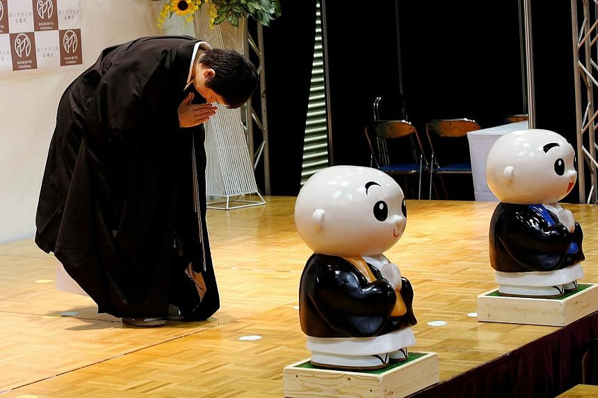 Female Buddhist monk Koyu Osawa, winner of the Handsomest Monk Contest, bows to spectators during the contest at the Life Ending Industry Expo in Tokyo.