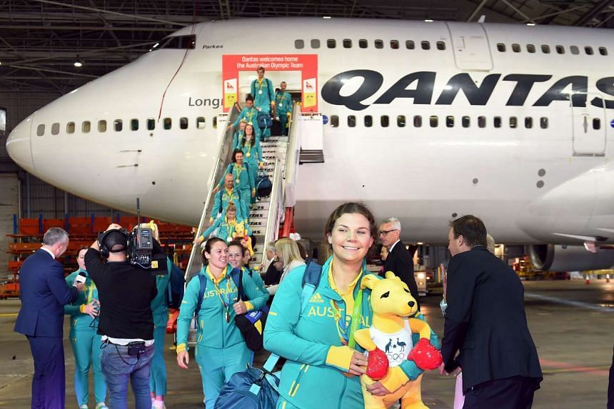 Australian gold medalist Catherine Skinner smiles as she arrives with other members of the Olympic team in Sydney on Aug 24.