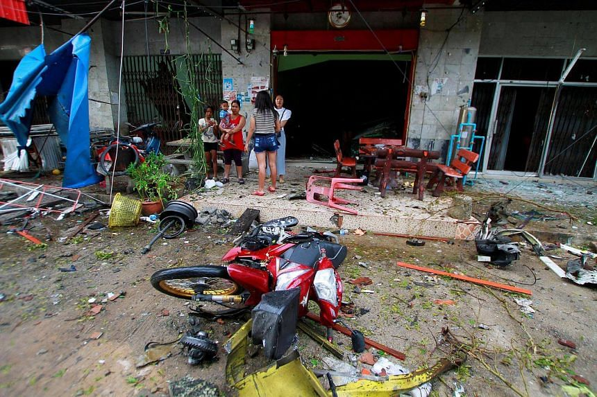 People stand at the scene after a blast outside a hotel in the southern province of Pattani, Thailand on Aug 24.