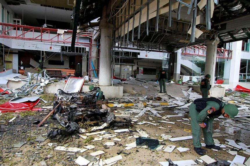 Thai soldiers inspect the scene of a car bomb blast outside a hotel in the southern province of Pattani, Thailand on Aug 24.