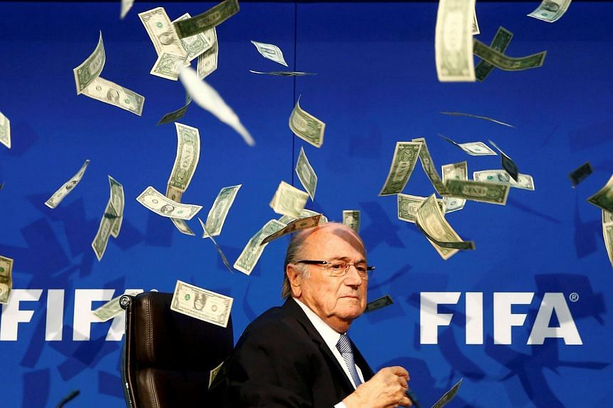 British comedian known as Lee Nelson (unseen) throws banknotes at Fifa President Sepp Blatter as he arrives for a news conference at the Fifa headquarters in Zurich, Switzerland, on July 20, 2015.