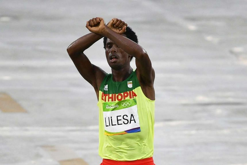 Lilesa crossed his arms as he finished the marathon (above) in a symbolic protest against the repressive Ethiopian regime.