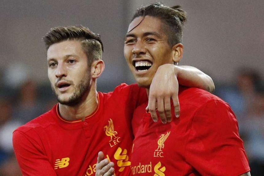 Liverpool's Roberto Firmino celebrates scoring their second goal with Adam Lallana.