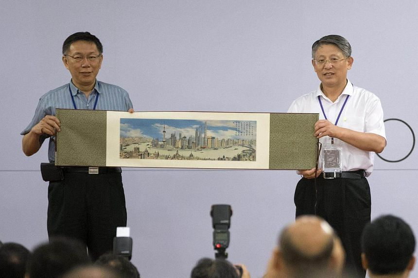 Taipei city Mayor Ko Wen-je (left) displays a Shanghai poster map received from Shanghai official Sha Hailin during a dinner at the city hall in Taipei, Taiwan on August 22.