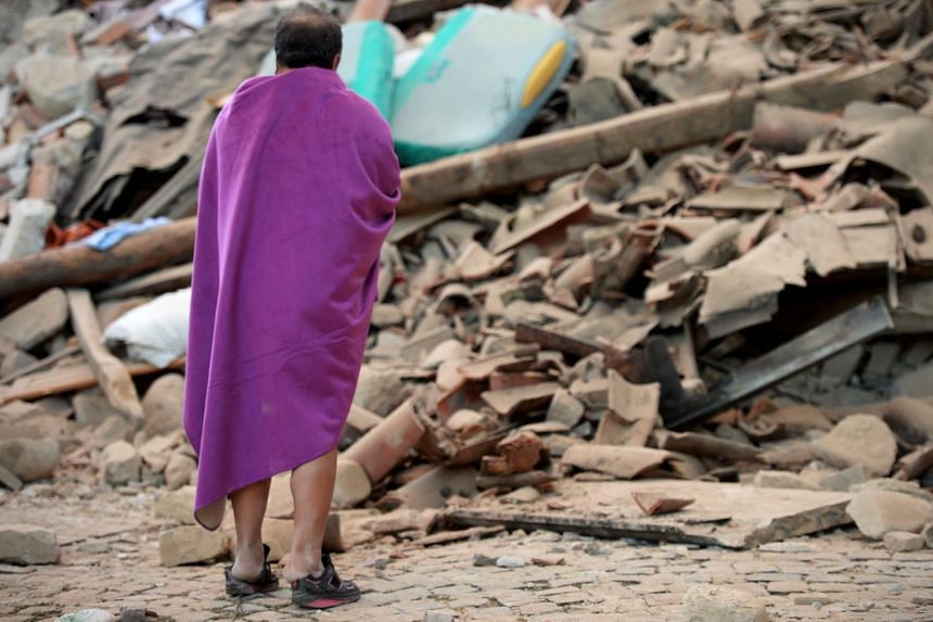 A man stands among the rubble of a house after a strong heartquake hit Amatrice on Aug 24.