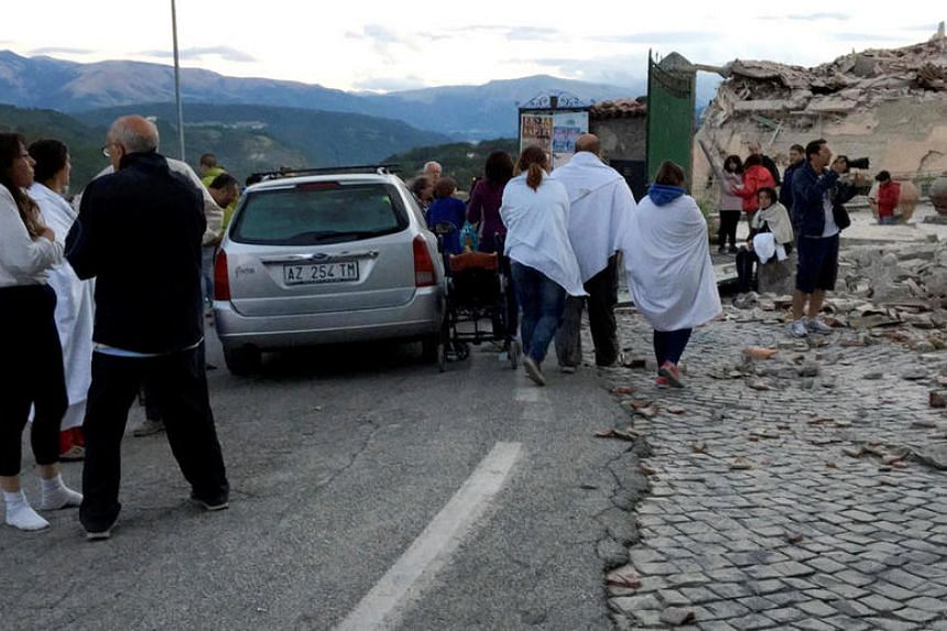 People stand along a road following a quake in Amatrice, central Italy, on Aug 24.
