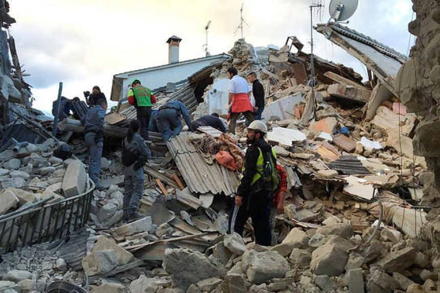 Rescuers work at a collapsed house following a quake in Amatrice, central Italy, on Aug 24.