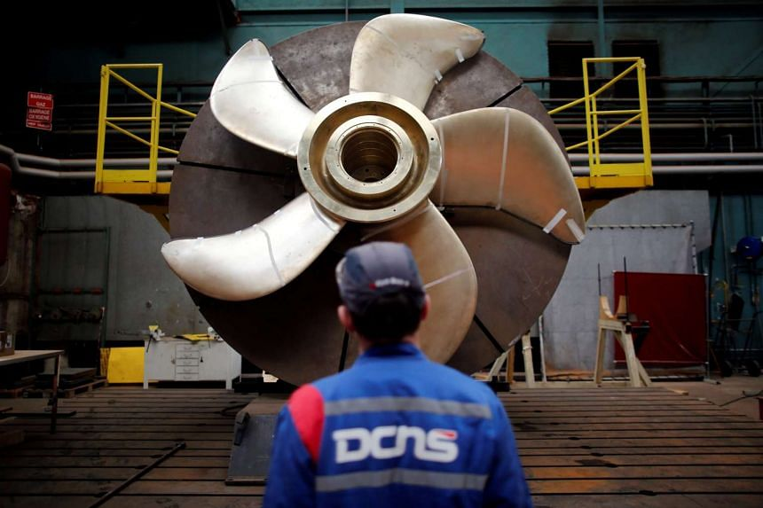 An employee looks at the propeller of a Scorpene submarine at the industrial site of the naval defence company and shipbuilder DCNS in La Montagne, France on April 26, 2016.