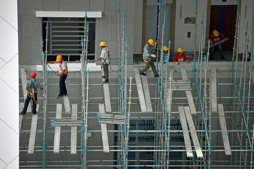 Construction workers standing precariously on a single narrow platform at a construction site along Waterloo Street on Feb 14, 2015.