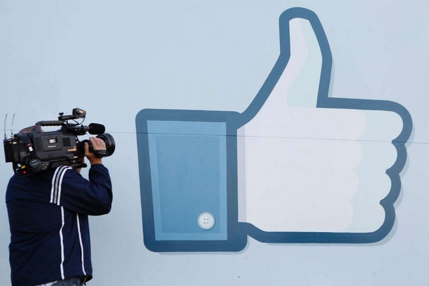 """Facebook's """"like"""" button logo displayed at the entrance of the company headquarters in Menlo Park, California."""