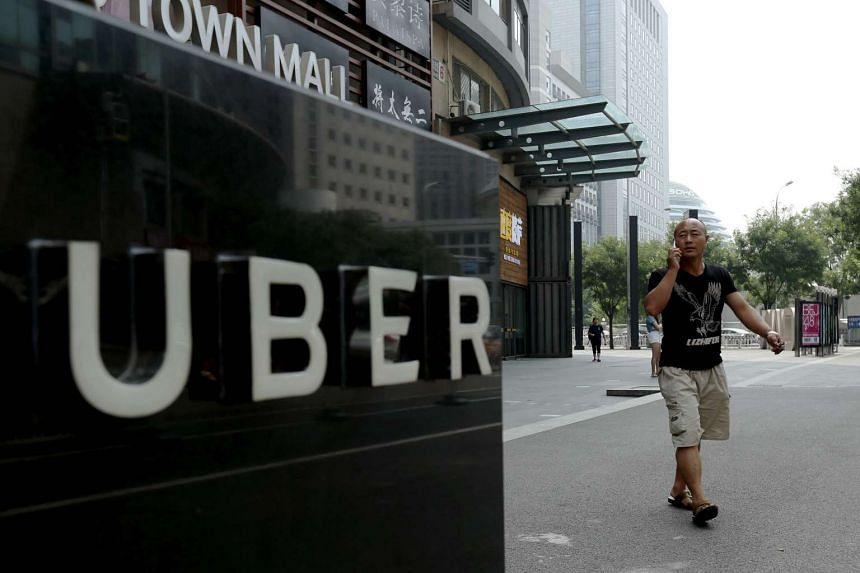 A man walking past an Uber sign outside a shopping mall in Beijing on Aug 1, 2016.