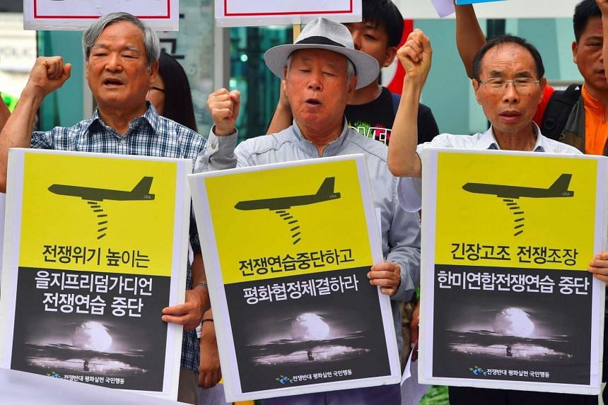 """Chitraveni Kumar: Anti-war activists shout slogans with placards reading """"Stop war exercise"""" during a rally denouncing the annual Ulchi Freedom Guardian joint US-South Korea military exercise, near the US embassy in Seoul on August 22."""