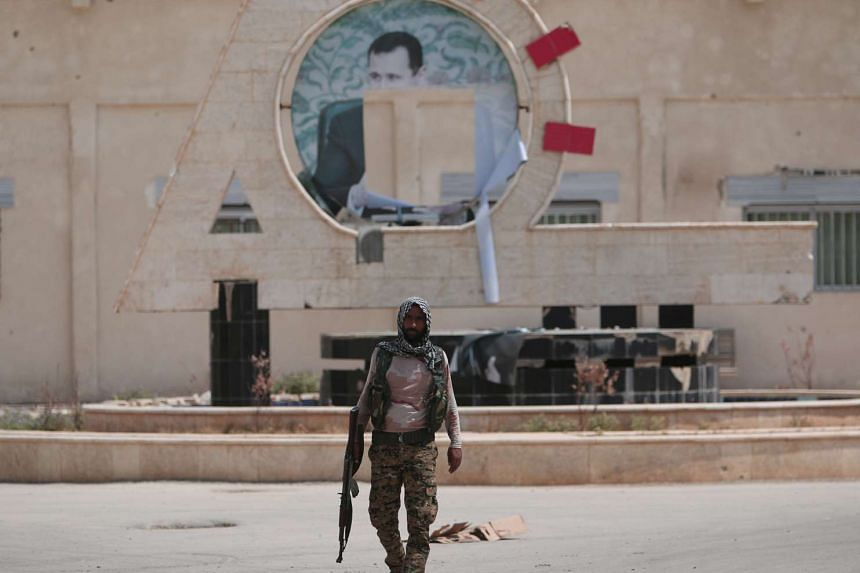 A Kurdish fighter from the People's Protection Units carries his weapon as he walks at the faculty of economics where a defaced picture of Syrian President Bashar al-Assad is seen in the background, in the Ghwairan neighborhood of Hasaka, Syria, Augu