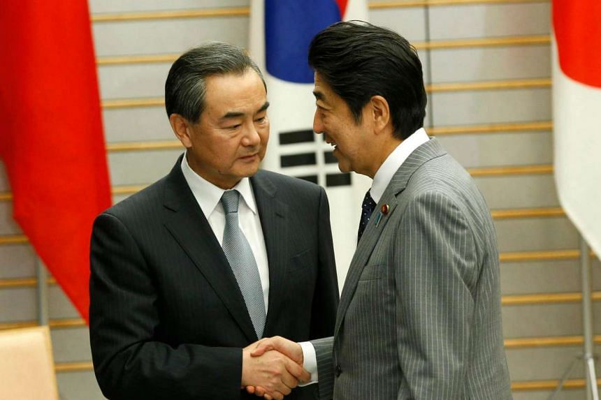 Japanese Prime Minister Shinzo Abe (right) shaking hands with Chinese Foreign Minister Wang Yi during their meeting in Tokyo, Japan on Aug 24, 2016.