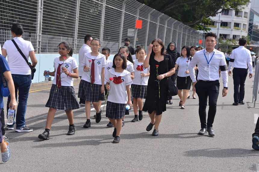 Pupils and teachers from Sengkang Primary School holding flowers walking towards Parliament House to pay their last respects to Mr S R Nathan.