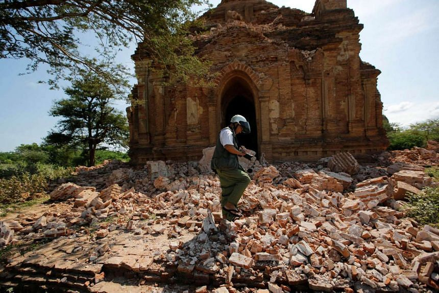 A photographer walks outside a collapsed pagoda, on August 25, after an earthquake struck Bagan, Myanmar the day before.