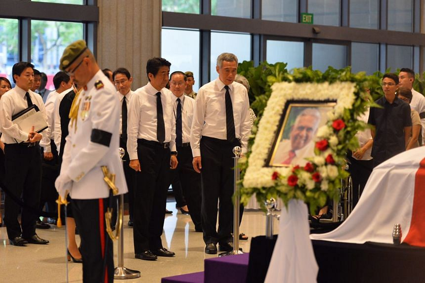 Japanese Prime Minister Shinzo Abe and Prime Minister Lee Hsien Loong pay respects to former president S R Nathan at the Parliament House on Aug 25, 2016.
