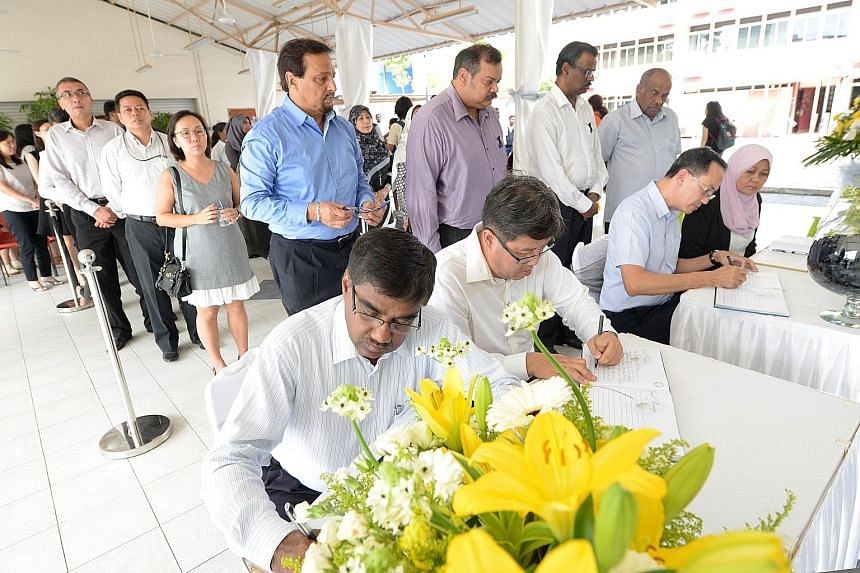 Senior Minister of State for Defence and Foreign Affairs Maliki Osman (at right in dark shirt) and leaders from the 10 faiths represented in the Inter-Religious Organisation holding a memorial service for Mr Nathan at the group's Maxwell Road office