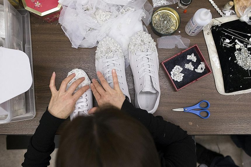 An employee at Kleinfeld Bridal in New York applying decorative elements to running shoes (left) for a bride to wear under her wedding gown.