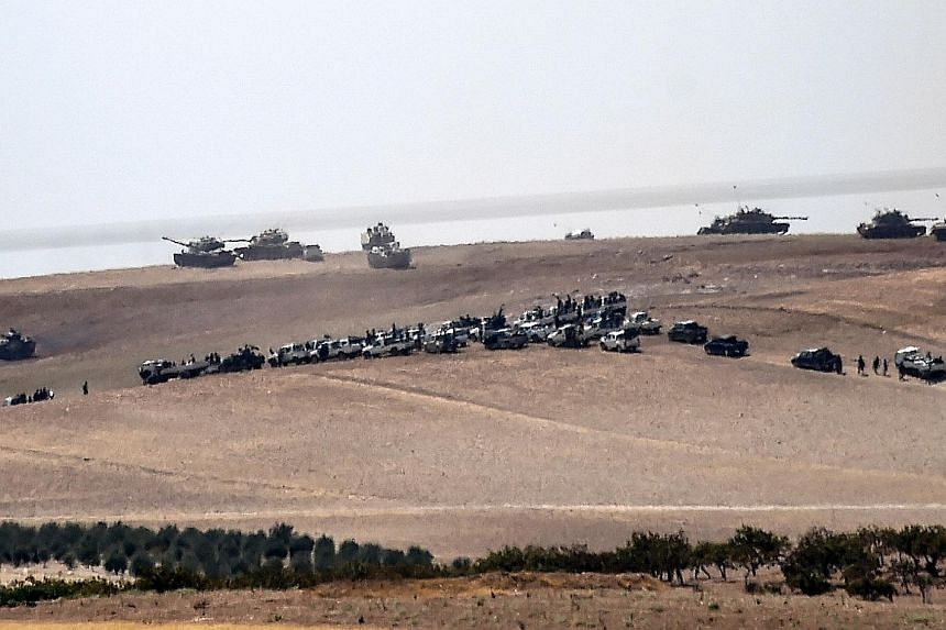 Turkish tanks and Syrian rebel fighter trucks assemble 2km west of the Turkish-Syrian border before launching their cross-border offensive on the Syrian town of Jarabulus, an ISIS stronghold.