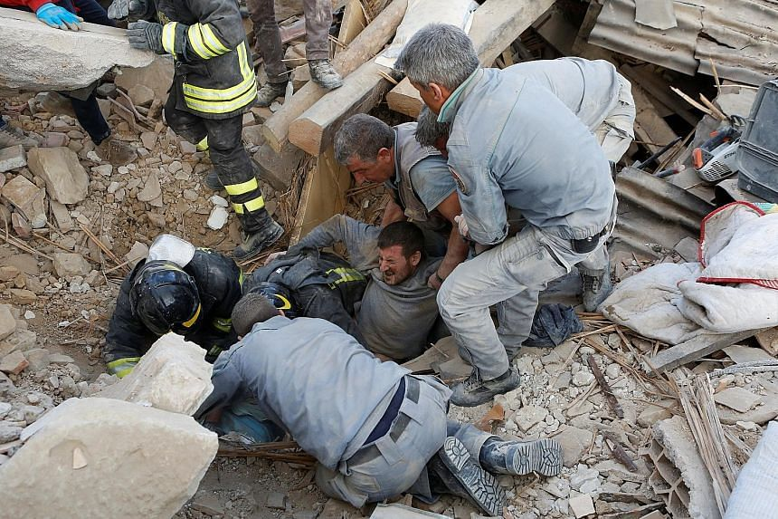 A survivor being rescued from the ruins in Amatrice, a hilltop beauty spot, following an earthquake in central Italy yesterday.