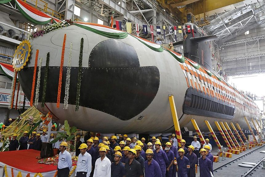 Employees standing in front of the Indian Navy's first Scorpene submarine before it was undocked from Mazagon Docks in Mumbai last year. Variants of the Scorpene-class DCNS submarine are used by Malaysia and Chile. Brazil is also due to deploy the ve