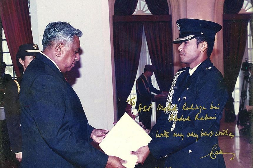 Mr Nathan giving Mr Redhza his appointment certificate when the latter was made an honorary aide-de-camp in 2001 after his stint as full-time ADC. The President later wrote a message on the photo as a keepsake for Mr Redhza.