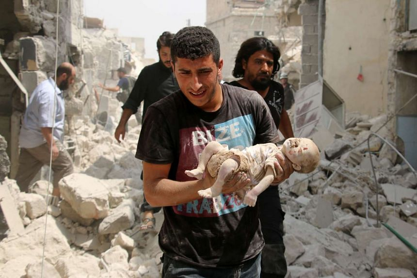 A Syrian man carries a dead baby from the rubble of buildings following the barrel bomb attack.