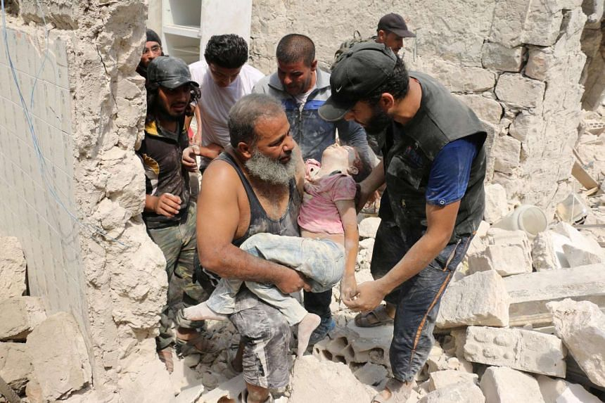 Syrians carry a wounded child from the rubble of buildings following the barrel bomb attack.