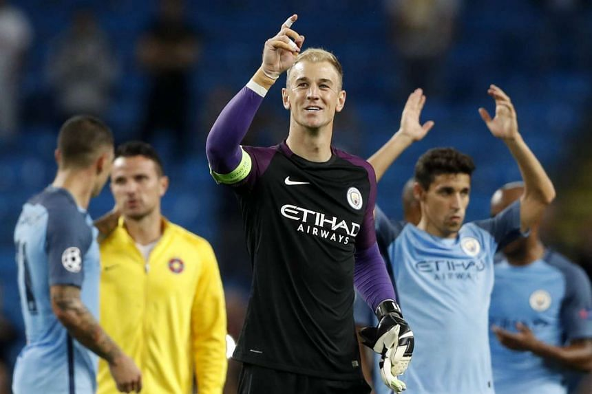 Manchester City's Joe Hart points to fans as he celebrates at the end of the match.