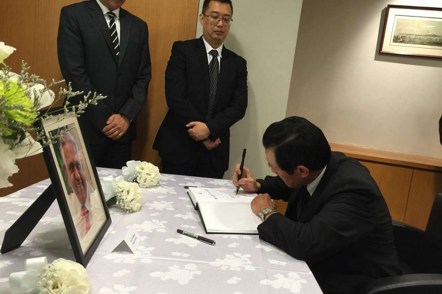 Former Taiwan President Ma Ying-jeou (seated) penning his condolence message on Aug 25, 2016 at the Singapore Trade Office in Taipei. Standing beside him are (from left): Director of General Affairs, Mr Lim Kwang Tang, and Trade Representative, Mr Si