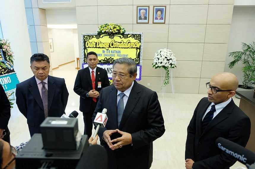 Former Indonesia president Susilo Bambang Yudhoyono (centre) speaks to reporters after he signs the condolence book for former president S R Nathan at the Singapore Embassy in Jakarta on Aug 25.