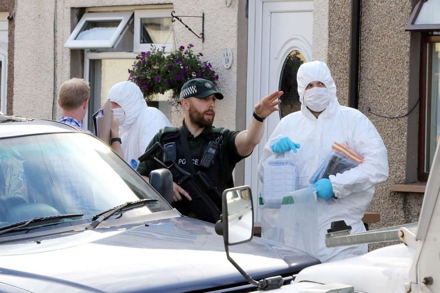 Police forensic officers carry evidence from a residential address in Larne, County Antrim, Northern Ireland, on Aug 24, 2016.