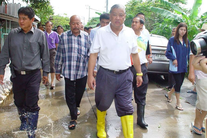 Mr Sukhumbhand Paribatra (in yellow boots) is under investigation for alleged graft.
