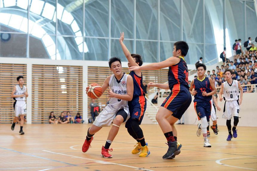 Presbyterian High's captain and centre, Kovan Toh (in white) dribbles past the ACS (Barker Road) defense.