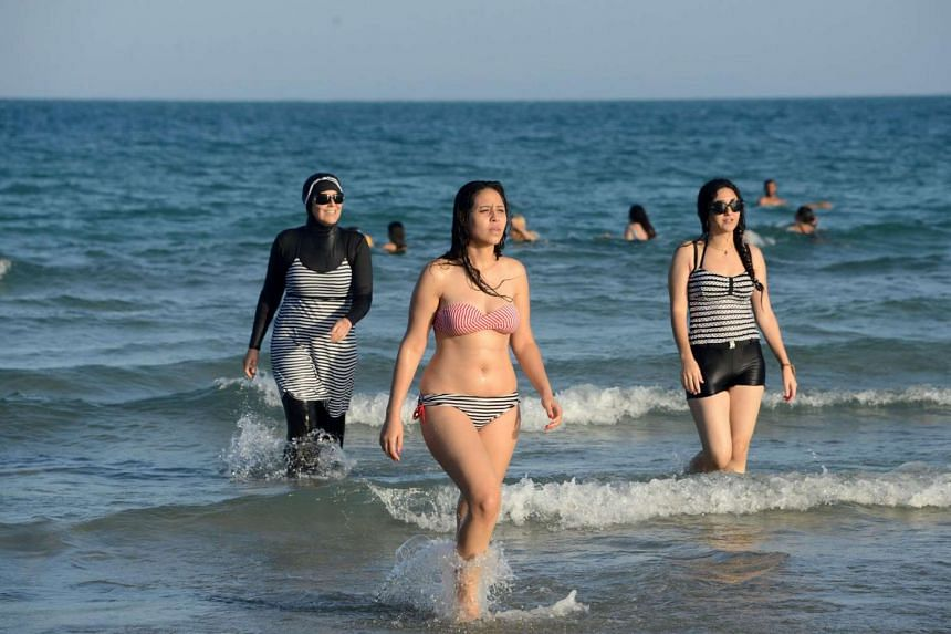"""This file photo taken on August 16, 2016 shows Tunisian women, one (left) wearing a """"burkini"""", a full-body swimsuit designed for Muslim women, walking in the water at Ghar El Melh beach near Bizerte, north-east of the capital Tunis."""