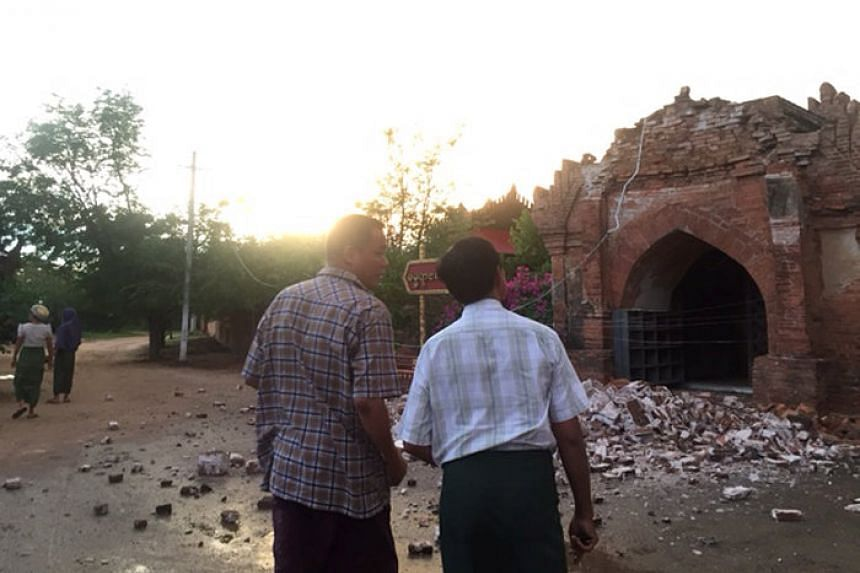 Two men look at a collapsed entrance of a pagoda after an earthquake in Bagan, Myanmar, Aug 24, 2016.