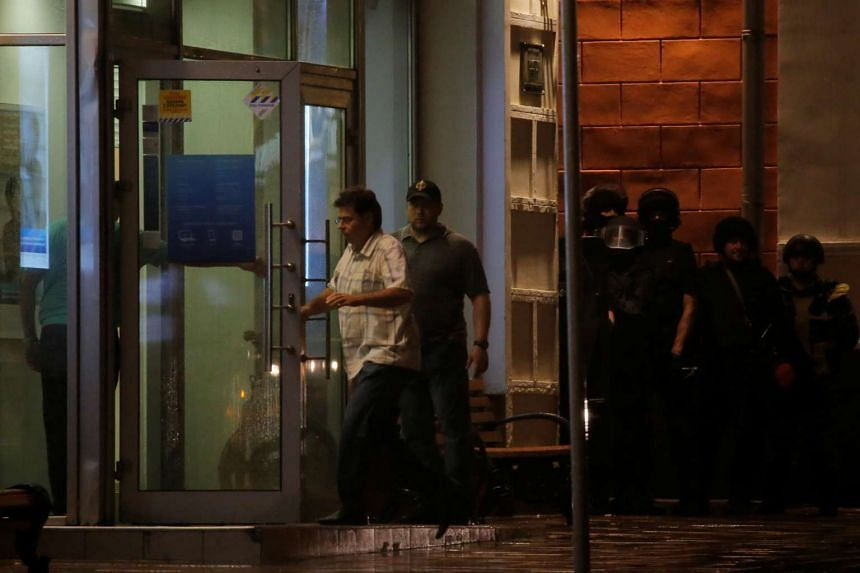 Negotiators enter a Citibank branch, seized by an unknown man who threatened to blow himself up, in central Moscow, Aug 24, 2016.