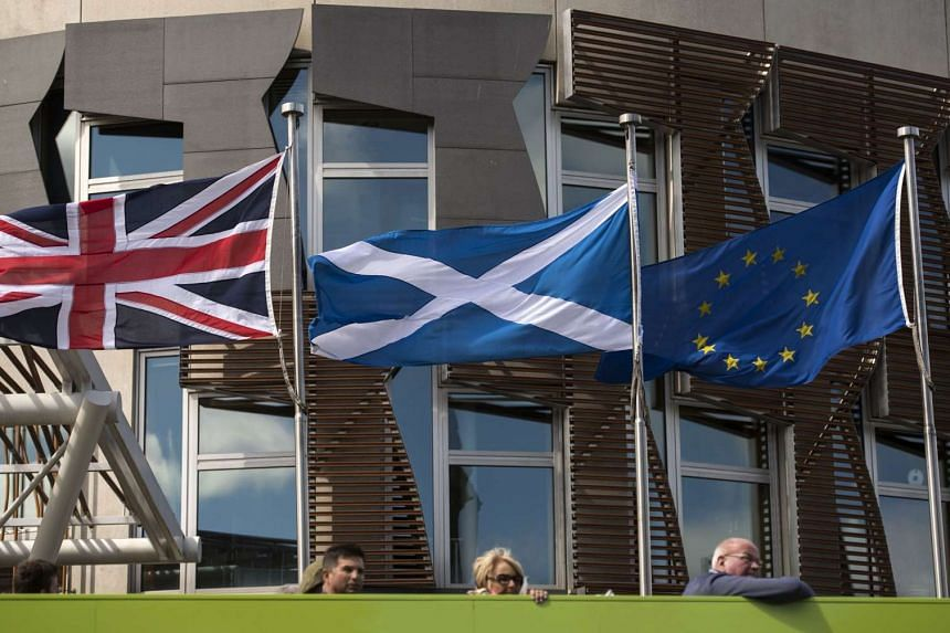 A Scottish Saltire (centre) flies between a British Union flag (left) and an EU flag in front of the Scottish Parliament building in Edinburgh, Scotland, on June 27, 2016.