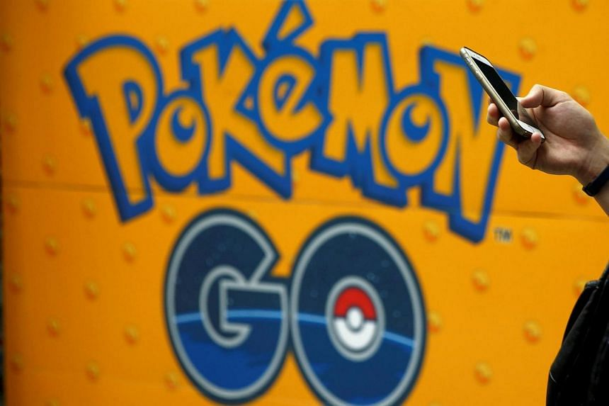 A man uses a mobile phone in front of an advertisement board bearing the image of Pokemon Go at an electronic shop in Tokyo, Japan, on July 27.