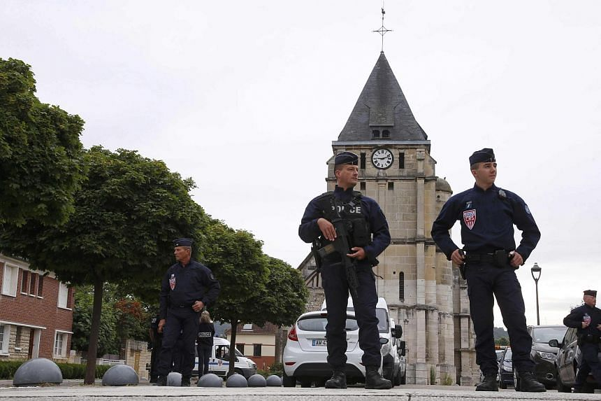 French CRS police stand guard in front of the church a day after a hostage-taking in Saint-Etienne-du-Rouvray near Rouen in Normandy, France.