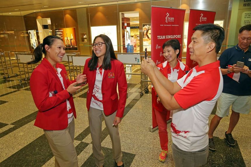 Minister for Social and Family Development Tan Chuan-Jin (right) interviews sailor Sara Tan (left) at Changi Airport. Sailor Amanda Ng and Minister for Culture, Community and Youth Grace Fu look on.