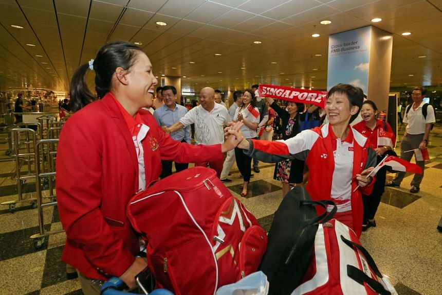 Above: Surrounded by athletes' family members and friends, Minister for Culture, Community and Youth Grace Fu clasping hands with sailor Sara Tan as the final batch of Team Singapore's Olympic athletes arrived at Changi Airport yesterday.