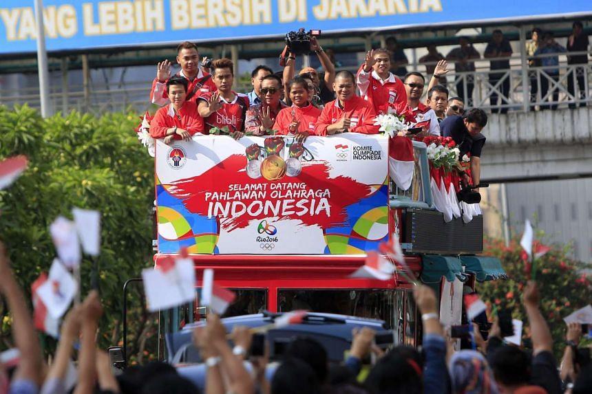 Above: Members of the Indonesian Olympic badminton team, including gold medallists Liliyana Natsir (left) and Tontowi Ahmad (third from left) wave from a bus while being paraded down a street in Jakarta yesterday.